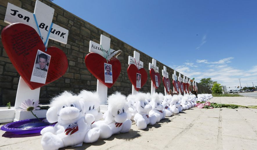 A row of crosses stands along Alameda Avenue near the intersection of Sable Boulevard to honor the 12 victims of the massacre at a nearby movie theatre and to mark the third anniversary of the killing spree, Monday, July 20, 2015, in Aurora, Colo. James Holmes, who had been working toward his Ph.D. in neuroscience, could get the death penalty for the massacre that left 12 people dead and dozens of others wounded early Friday, July 20, 2012. (AP Photo/David Zalubowski)