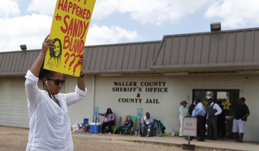 Brandi Holmes, of Houston, carries a sign as she protests in front of the Waller County Sheriff's Office and county jail on Monday, July 20, 2015, in Hempstead, Texas. Authorities said Bland hanged herself in the jail three days after being pulled over by police for a traffic violation and then arrested for allegedly kicking an officer during the stop. Bland's family is ordering an independent autopsy, lawyers said. (Karen Warren/Houston Chronicle via AP) MANDATORY CREDIT