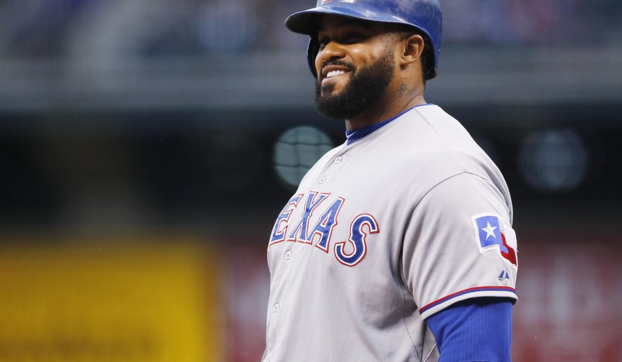 Texas Rangers' Prince Fielder jokes with Colorado Rockies catcher Nick Hundley as Fielder steps to the plate in the first inning of a baseball game Monday, July 20, 2015, in Denver. (AP Photo/David Zalubowski)