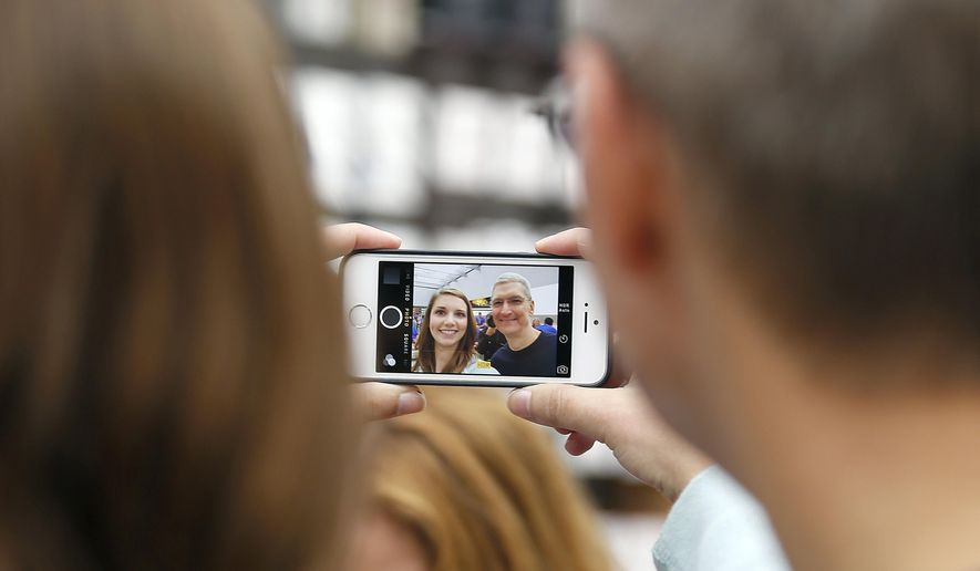 In this Sept. 19, 2014, file photo, Apple CEO Tim Cook, right, takes a photo with an Apple employee during the launch and sale of the new iPhone 6 at an Apple store in Palo Alto, Calif. (AP Photo/Tony Avelar, File)