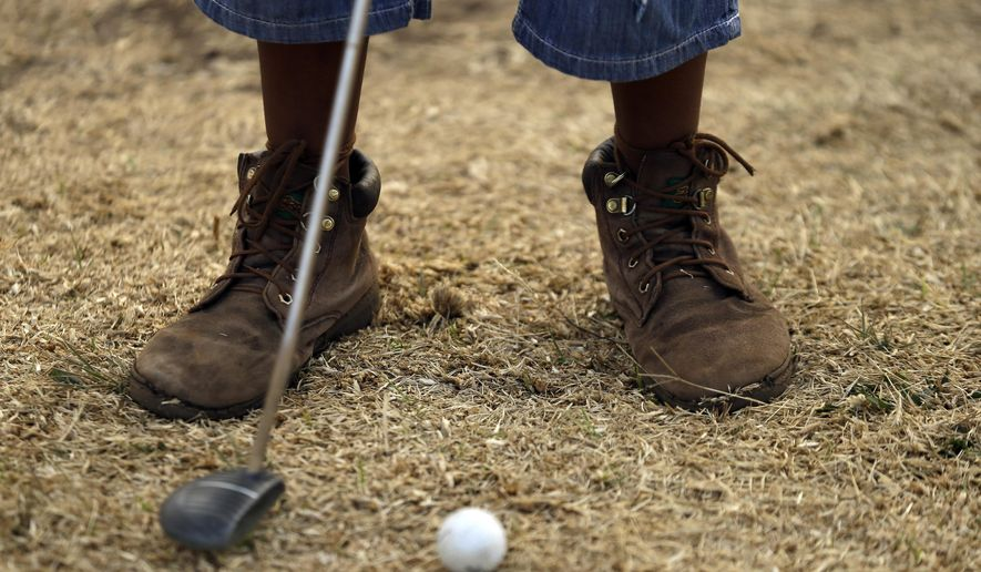 Ten-year-old Amohela Mokoena, plays a putt during a golf game at a park in Katlehong township, east of Johannesburg, South Africa, Thursday, July 16, 2015. At first the township children only watched as their retired neighbour and former golf caddie, Wynand Morudu,  hit a ball up and down the open field then soon they joined in, forming an amateur golf training school in the working class South African township. (AP Photo/Themba Hadebe)