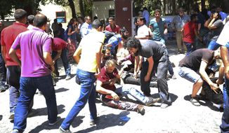 People help the wounded after an explosion in the southeastern Turkish city of Suruc near the Syrian border, Turkey, Monday, July 20, 2015. (AP Photo/Ozcan Soysal)