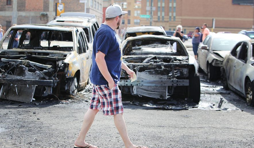 An onlooker walks through a parking lot next to burned out vehicles Sunday, July 19, 2015, in Detroit. The owners of the vehicles were at a Detroit Tigers baseball game when the fire occurred, according to the Detroit Free Press. (Regina H. Boone/Detroit Free Press via AP)  DETROIT NEWS OUT; TV OUT; MAGS OUT; NO SALES; MANDATORY CREDIT DETROIT FREE PRESS