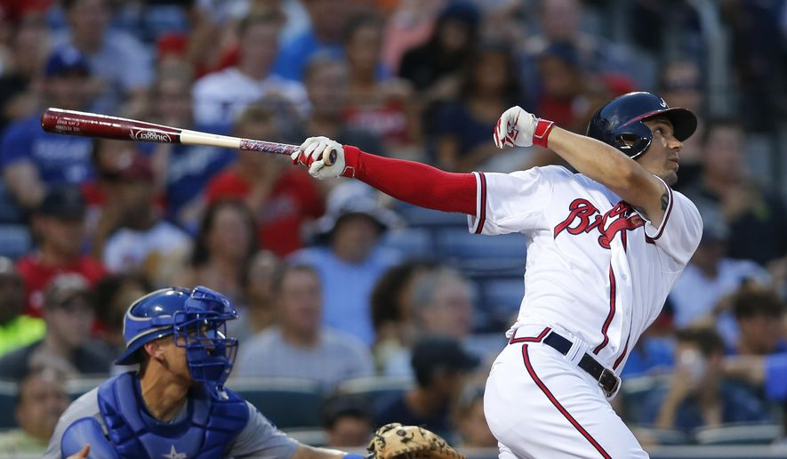 Atlanta Braves's Jace Peterson, right, follows through on a two-run double as Los Angeles Dodgers catcher Austin Barnes looks on in the fourth inning of a baseball game Monday, July 20, 2015, in Atlanta. (AP Photo/John Bazemore)