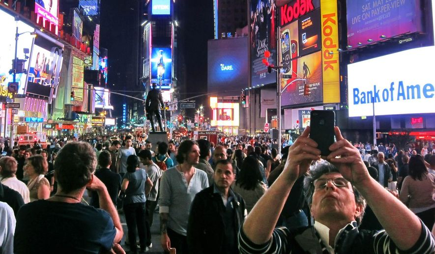 FILE - In this May 12, 2012, file photo, a man takes a photo in front of the statue of theatrical legend George M. Cohan in the heart of New York's theater district. It's been a month of bad behavior among theatergoers in New York, including a teenager's attempt to charge his phone in a dummy outlet on a stage and an evening when Patti LuPone caught someone texting during her play and swiped the phone out of the patron's hand. (AP Photo/Chuck Zoeller, File)