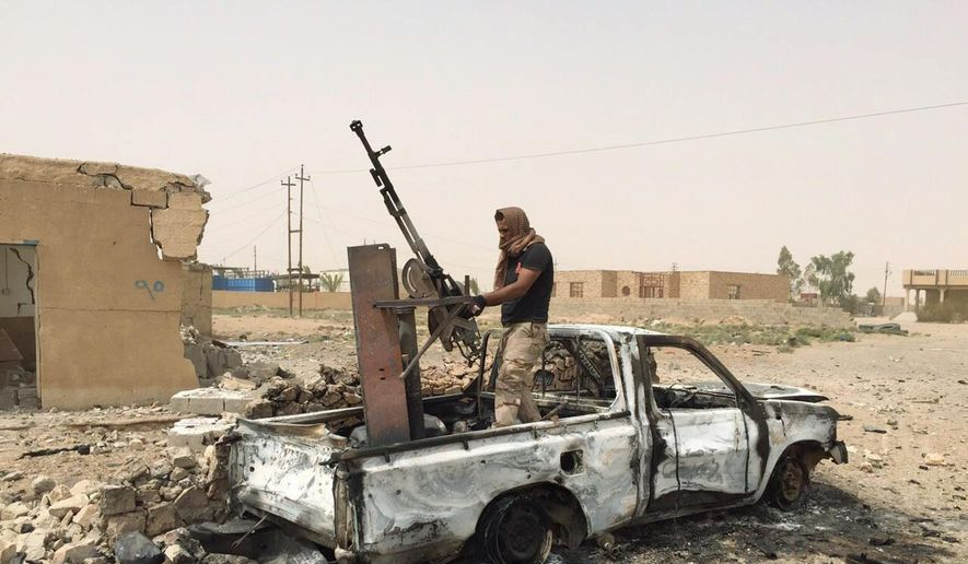 A militiaman allied with the Iraqi security forces dismantles a weapon from a destroyed vehicle belonging to the Islamic State group following a U.S.-led coalition airstrike against IS positions in southern Ramadi, Anbar province, Iraq, Monday, July 20, 2015. Iraqi security officials said that militants from the Islamic State group blew up a sports stadium near the militant-held city of Ramadi. (AP Photo) ** FILE **