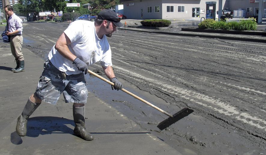 Kevin Dente cleans mud from the sidewalk in front of his store on North Main Street Monday July 20, 2015, in Barre, Vt.  Overnight flooding in Barre forced several people to be evacuated from homes their homes. Flooding in Barre and elsewhere in Central Vermont prompted the activation of the state Emergency Operations Center. (AP Photo/Wilson Ring)