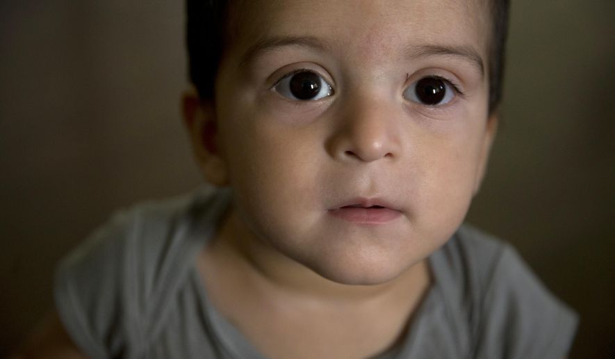 FILE - In this June 8, 2015, file photo, 1-year-old Joshua Tinoco pauses while playing at his relative's home in Los Angeles. The U.S. government has agreed to shelve efforts to deport Tinoco whose teenage mother has been allowed to remain in the country and apply for permanent residency. (AP Photo/Jae C. Hong, File)