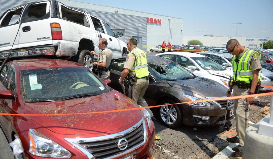 An SUV rests on top of cars at a Nissan dealership after it veered across Interstate 15 and rolled onto the vehicles in Victorville, Calif, Sunday, July 19, 2015. A child was ejected in the crash and transported by Mercy Air, according to the Victor Valley Daily Press. (David Pardo/The Victor Valley Daily Press via AP) MANDATORY CREDIT