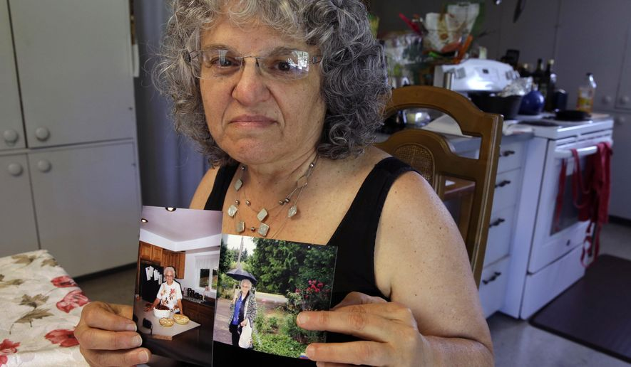 In this July 1, 2015 photo, Roslyn Duffy poses for a photo holding two photos of her late mother, Evelyn Nappa, at her home in Seattle. Duffy had to scramble to find a home willing to take Medicaid payments after her mother was evicted from a Seattle assisted-living facility. The stress and the change of surroundings strained her mother's health, Duffy said, and six weeks after moving, she was dead. (AP Photo/Ted S. Warren)