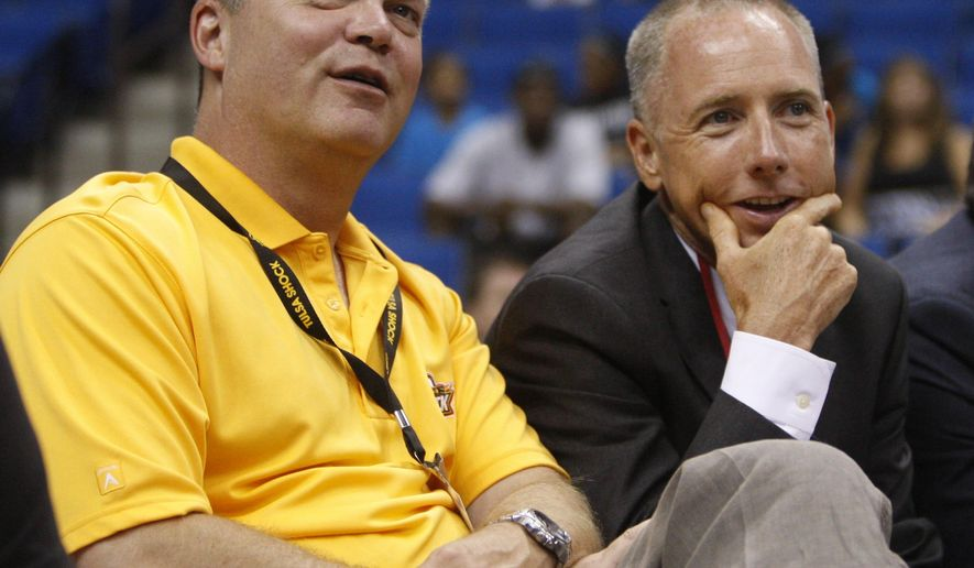 FILE - In this July 28, 2011, file photo, Bill Cameron, left, and David Box, majority owners of the Tulsa Shock, watch from the sidelines during a WNBA basketball game in Tulsa, Okla. Tulsa Shock majority owner Bill Cameron announced plans Monday, July 20, 2015,  to move the WNBA franchise to the Dallas-Fort Worth market. (AP Photo/Sue Ogrocki, File)