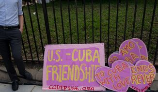 Signs in favor of United States and Cuba relations sit on the ground across the street from the new Cuban Embassy in Washington, Monday, July 20, 2015. The United States and Cuba restored full diplomatic relations Monday after more than five decades of frosty relations rooted in the Cold War. (AP Photo/Andrew Harnik)