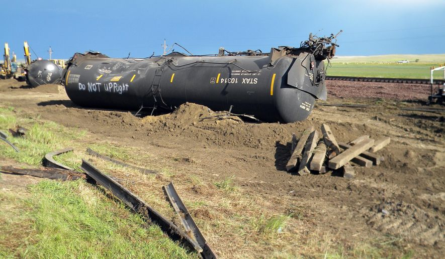 Derailed oil tanker cars lie off track near Culbertson, Mont., Friday, July 17, 2015. The tank cars were hauling fuel from North Dakota and derailed Thursday in rural northeastern Montana, authorities said. (AP Photo/Richard Peterson)