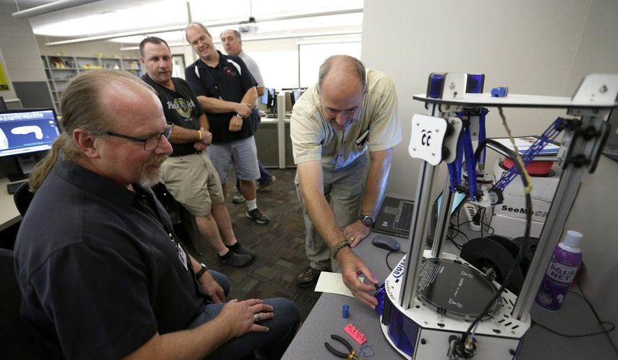 Mechanical Design instructors Jeff Laurich, left, and Dean Sommerfeld demonstrate a 3D printer to area high school Tech Ed teachers Wednesday, July 15, 2015, Fox Valley Technical College in Grand Chute, Wis. The technology has allowed them to create prosthetic hands for children in need. (Dan Powers/Post-Crescent Media via AP)