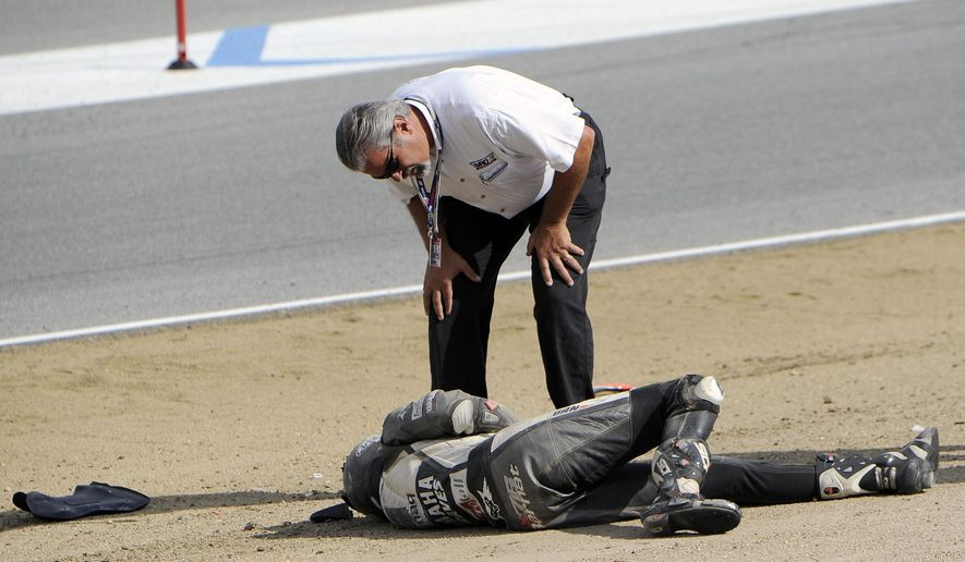 In this Sunday, July 19, 2015, photo, a race official looks at Spanish rider Bernat Martinez after a chain reaction crash on the first lap of a World Superbike race at Mazda Raceway at Laguna Seca in Monterey, Calif. Two Spanish racers were killed in the crash. Race organizers MotoAmerica identified the dead as 35-year-old Bernat Martinez and 27-year-old Daniel Rivas Fernandez. Both were taken to hospitals, where they later died.  (Nic Coury/Monterey County Weekly via AP) MANDATORY CREDIT FOR PAPER AND PHOTOGRAPHER. MONTEREY HERALD OUT , SALINAS CALIFORNIAN OUT , SANTA CRUZ SENTINEL OUT , SAN JOSE MERCURY OUT , LOCAL TV OUT