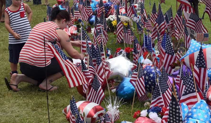 Isaac Pierce watches his mother, Stefanie Pierce, as she straightens an American flag at a makeshift memorial at the Armed Forces Career Center, Sunday, July 19, 2015, in Chattanooga, Tenn. Muhammad Youssef Abdulazeez attacked two military facilities, including the career center, last week in a shooting rampage that killed a U.S. Navy sailor and four Marines. (John Rawlston/Chattanooga Times Free Press via AP)