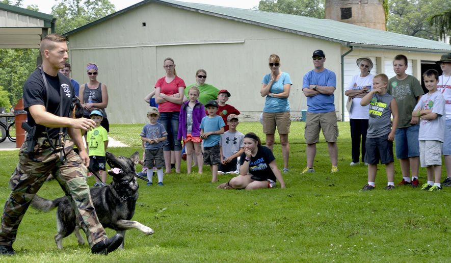 In this June 6, 2015 photo, Effingham, Ill., police officer Andy Warner and his K-9 partner, Narco, work on obedience skills in front of area kids and parents in the 23rd annual JAKES event at Ballard Nature Center in Altamont, Ill. The JAKES event included archery, fishing, shotgun target shoot, BB gun shoot, turkey calling and tree stand climbing. (Bill Grimes/Effingham Daily News via AP)