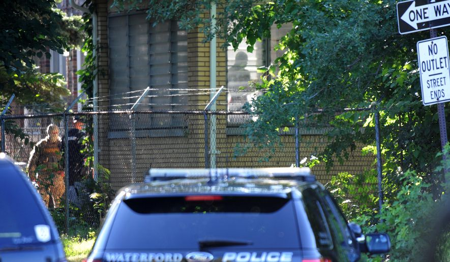 Members of the FBI and local law enforcement raid a home on Goldengate in Detroit, Michigan on Tuesday, July 21, 2015, as part of a widespread crackdown on a violent heroin ring. Federal, state and local law enforcement agencies raided several Detroit locations Tuesday as part of an effort to curb heroin sales. (Brandy Baker/The Detroit News via AP)