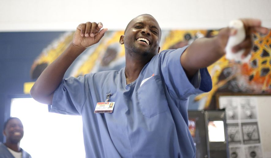 ADVANCE FOR WEEKEND OF JULY 25-26 AND THEREAFTER Joseph Montique sings Bob Marley's Three Little Birds with fellow inmates enrolled in the Music Therapy Program at the Wakulla Work Camp Correctional Institution, Monday, July 13, 2015, in Crawfordville, Fla. Dubbed the Behind the Wire Choir, the group consists of about 20 inmates. A full band, including piano and keyboard, bass and electric guitarists, three acoustic guitars and a drummer, provided a musical canvas for the chorus. (Joe Rondone/Tallahassee Democrat via AP)