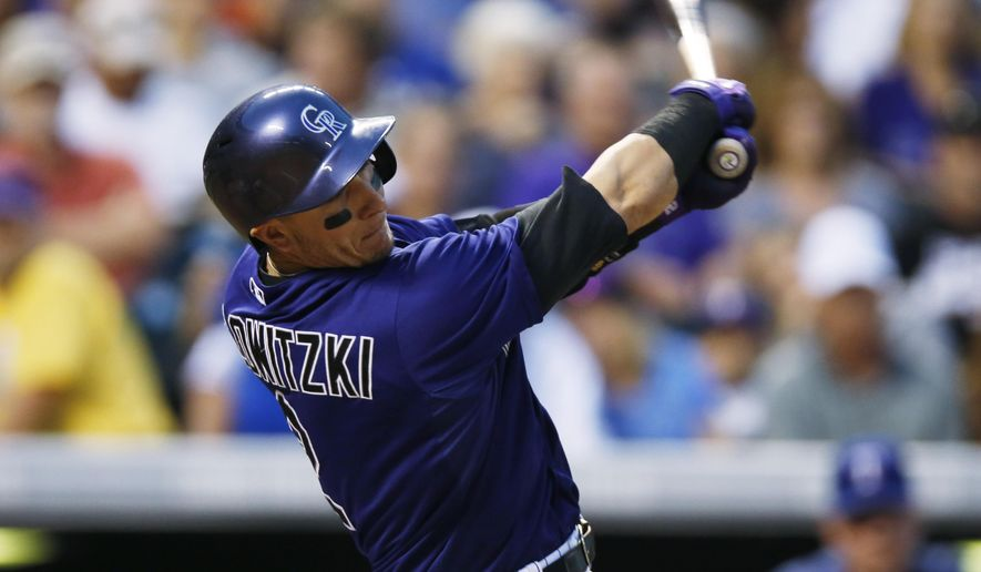 Colorado Rockies' Troy Tulowitzki  swings at pitch from Texas Rangers pitcher Nick Martinez in the fourth inning of a baseball game Monday, July 20, 2015, in Denver. (AP Photo/David Zalubowski)