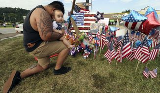 Bryan Thaboua kneels with his 8-month-old son Cooper Thaboua on Monday, July 20, 2015, in front of the Lee Highway memorial for last Thursday's Chattanooga, Tenn., shooting victims. Muhammad Youssef Abdulazeez attacked two military facilities on Thursday in a shooting rampage that killed several. (Dan Henry/Chattanooga Times Free Press via AP)