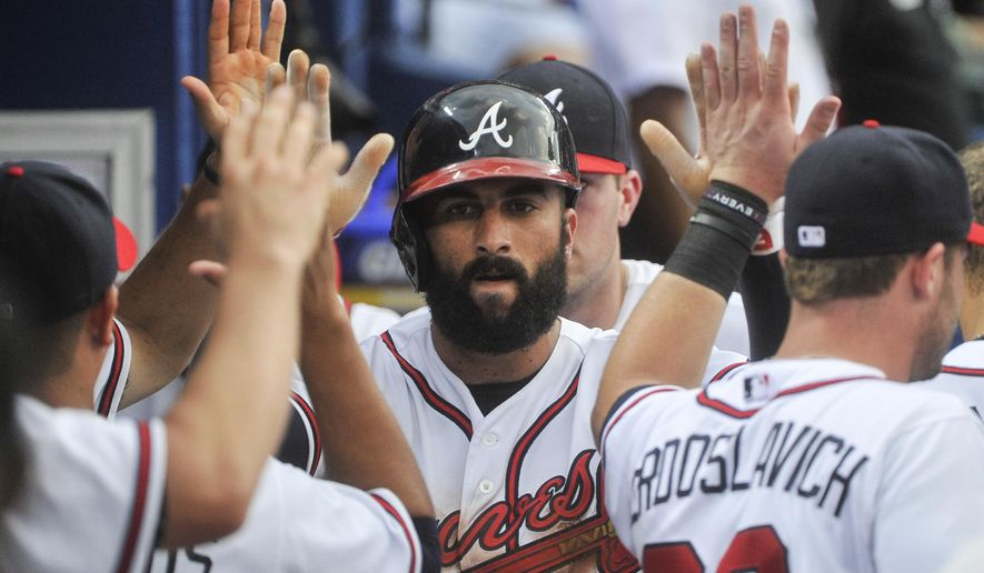 Atlanta Braves' Nick Markakis celebrates scoring against the Los Angeles Dodgers during the third inning of a baseball game, Tuesday, July 21, 2015, in Atlanta. (AP Photo/John Amis)