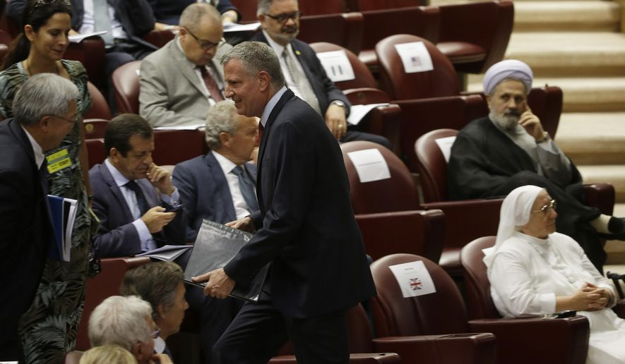 New York Mayor Bill de Blasio, center, arrives in the Synod Hall to attend a conference on Modern Slavery and Climate Change at the Vatican, Tuesday, July 21, 2015. Dozens of environmentally friendly mayors from around the world are meeting at the Vatican this week to bask in the star power of eco-Pope Francis and commit to reducing global warming and helping the urban poor deal with its effects. (AP Photo/Gregorio Borgia)