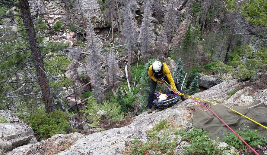 In this Monday, July 20, 2015 photo provided by the Rocky Mountain National Park, national park service staff rescue a 13-year-old girl after she hurt her leg while hiking with her dad at Rocky Mountain National Park. The teen's father hiked to find better cell phone reception and called for help. Rescue workers traveled over steep terrain impacted by the Fern Lake fire before finding the pair in the early hours of Monday morning. (Rocky Mountain National Park via AP)