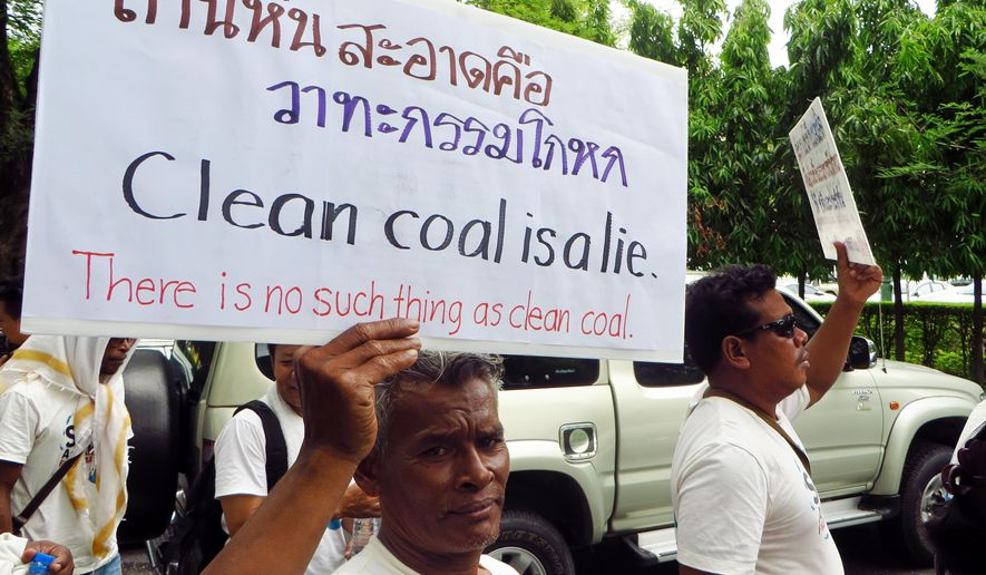 In this Monday July 20, 2015 photo, a protester holds a placard outside the Prime Minister's office in Bangkok during a demonstration opposing a proposed coal power plant in southern Thailand. The popular tourist beaches near southern Thailand's Andaman Coast may soon play host to an unlikely new fixture: an 800-megawatt coal power plant. The plans have sparked an outcry in the typically tranquil Krabi province, famed for its white sand and picturesque limestone cliffs. (AP Photo/Ted Andersen)