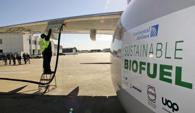 In this Jan. 7, 2009, file photo, Monte Hawkins prepares to remove the fuel line attached to a Continental Airlines jet for the first biofuel-powered demonstration flight of a U.S. commercial airliner, at Bush Intercontinental Airport in Houston. Many in the industry believe that without a replacement for jet fuel, growth in air travel could be threatened by forthcoming rules that limit global aircraft emissions. (AP Photo/David J. Phillip, File)
