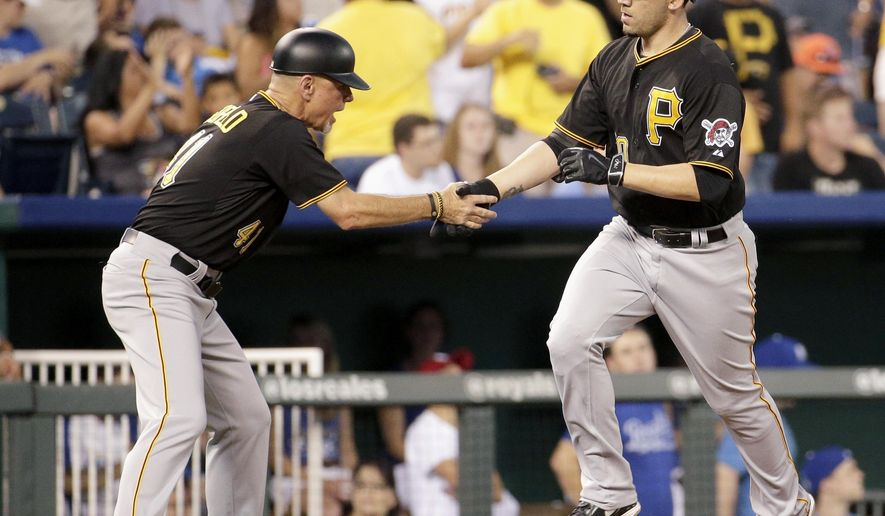 Pittsburgh Pirates' Travis Ishikawa, right, celebrates with third base coach Rick Sofield after hitting a two-run home run during the fifth inning of a baseball game Monday, July 20, 2015, in Kansas City, Mo. (AP Photo/Charlie Riedel)