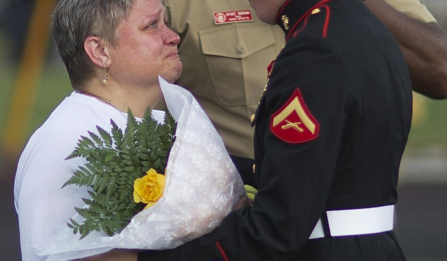 "Cathy Wells, left, the mother of Lance Cpl. Squire Wells, known as ""Skip,"" is embraced by Lance Cpl. Kurt Bright, one of Wells' best friends upon arriving for a memorial service for her son at Sprayberry High School where he attended, Tuesday, July 21, 2015, in Marietta, Ga. Crowds gathered at the suburban Atlanta high school to remember the Marine who was fatally shot in an attack on military facilities in Chattanooga, Tenn. (AP Photo/David Goldman)"