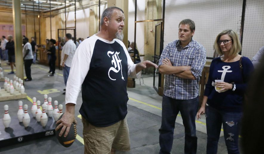 In a photo from June 19, 2015, in Hamtramck, Mich., Chris Hutt, left, explains the rules of Fowling, a sport Hutt created by combing football and bowling. Hutt believes he can make a buck off the game, opening the 34,000-square-foot Fowling Warehouse inside an industrial park in the Detroit enclave of Hamtramck. (AP Photo/Carlos Osorio)