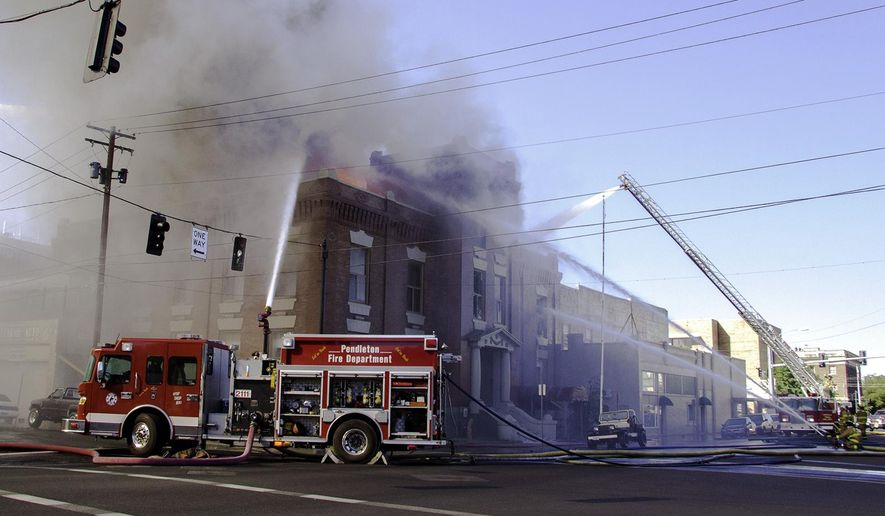 Pendleton firefighters spray water onto the old  City Hall after an explosion rocked the building, Tuesday, July 21, 2015 in Pendleton, Ore.  The explosion and fire were reported at about 8 a.m. Witnesses saw a man and a woman escape shortly after the loud blast.  At least one person was reported injured.   (Kathy Aney/East Oregonian via AP) MANDATORY CREDIT