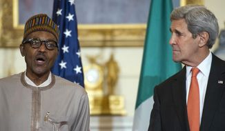 Secretary of State John Kerry looks on while Nigerian President Muhammadu Buhari makes a statement prior to their working lunch at the State Department in Washington, Tuesday, July 21, 2015. (AP Photo/Cliff Owen)