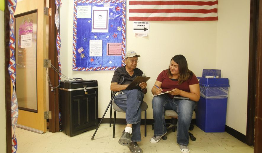 Tom Smith Sr. and his daughter Alissa Lee, fill out paper work, Friday, July 17, 2015, before voting at the Navajo Election Administration - Northern Agency Office in Shiprock, N.M. (Jon Austria/The Daily Times via AP)