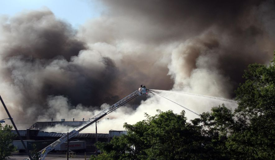 Firefighters battle a multiple alarm fire at a large warehouse in North Brunswick, N.J., Wednesday July 22, 2015. The warehouse fire in central New Jersey that was fueled by plastics, autos and household goods sent plumes of black smoke into the air Wednesday that were visible from space. (Mark R. Sullivan/Home News Tribune via AP)