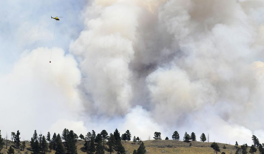 A helicopter approaches a wildfire near Townsend, Mont., Tuesday, July 21, 2015. The fire has closed a portion of U.S. Highway 12 and led to evacuation orders in the rural area. (Thom Bridge/The Independent Record via AP) MANDATORY CREDIT