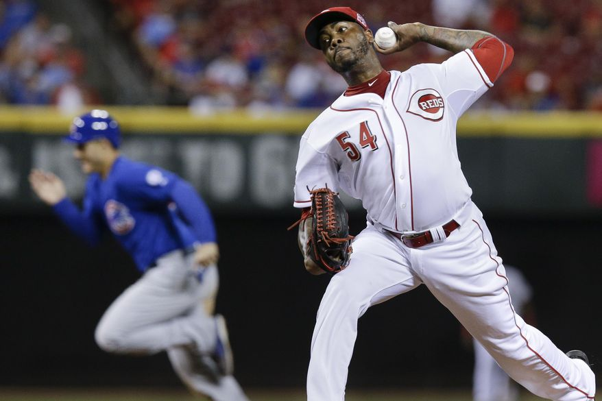 Cincinnati Reds relief pitcher Aroldis Chapman throws as Chicago Cubs' Anthony Rizzo steals third base in the ninth inning in the second game of a baseball doubleheader in Cincinnati, Wednesday, July 22, 2015.  (AP Photo/John Minchillo)