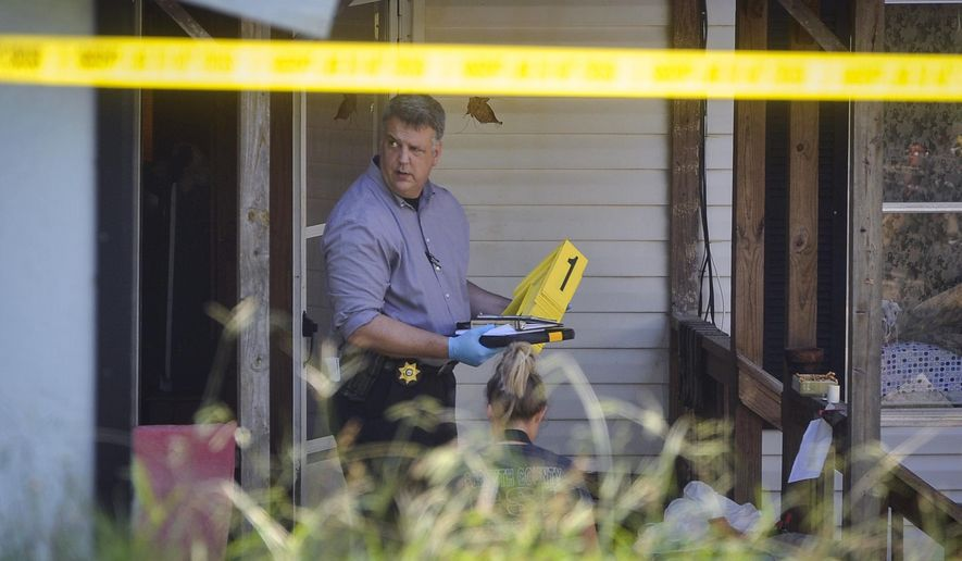 Law enforcement investigate the scene of a shooting at a home in Suwanee, Ga., Wednesday, July 22, 2015. A gunman killed a woman and two children and wounded another man before killing himself inside the suburban Atlanta home early Wednesday, Forsyth County Sheriff Duane Piper said. (AP Photo/John Amis)