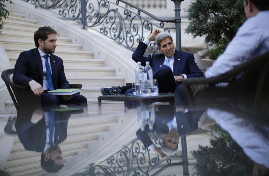 U.S. Secretary of State John Kerry (center) and State Department Chief of Staff Jon Finer (left) meet with members of the U.S. delegation at the garden of the Palais Coburg hotel where the Iran nuclear talks meetings are being held in Vienna on July 10, 2015. (Associated Press) **FILE**