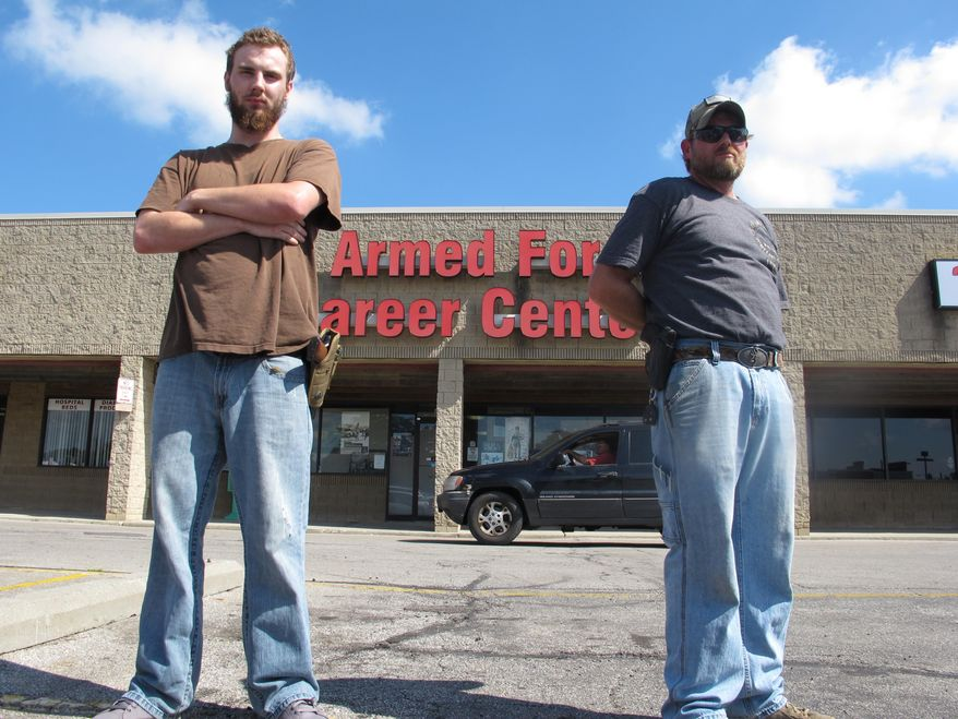 In this photo taken Tuesday, July 21, 2015, Allen Bowles, left, and Clint Janney stand guard outside a military recruiting center in Columbus, Ohio. The men are members of the 3 Percent Irregulars Militia, and say they plan to protect the center until the government provides its own security.(AP Photo/Andrew Welsh-Huggins)