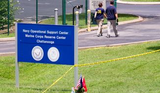 Investigators walk by the entrance of a Navy and Marine center in Chattanooga, Tenn., on Wednesday, July 22, 2015.  Law enforcement officials for the first time provided details about how Muhammad Youssef Abdulazeez crashed the gates with his car and opened fire on the service members inspecting equipment there, killing four Marines and one sailor. (AP Photo/Erik Schelzig)