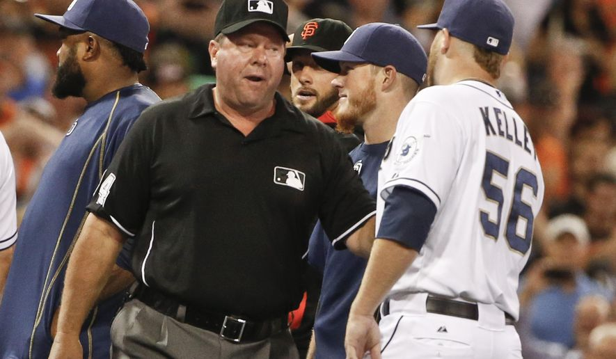 Umpire Sam Holbrook talks to San Diego Padres pitcher Shawn Kelley after both teams rushed the field in the eighth inning of a baseball game against the San Francisco Giants Tuesday, July 21, 2015, in San Diego. No punches were thrown and no one was ejected. (AP Photo/Lenny Ignelzi)