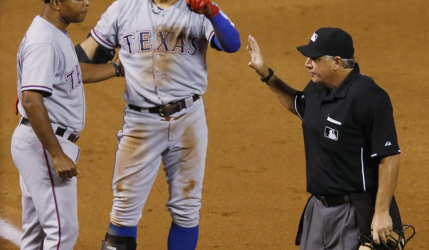 Texas Rangers third base coach Tony Beasley, left, congratulates Shin-Soo Choo after he hit a triple to complete the cycle, during the ninth inning of a baseball game against the Colorado Rockies on Tuesday, July 21, 2015, in Denver. (AP Photo/David Zalubowski)