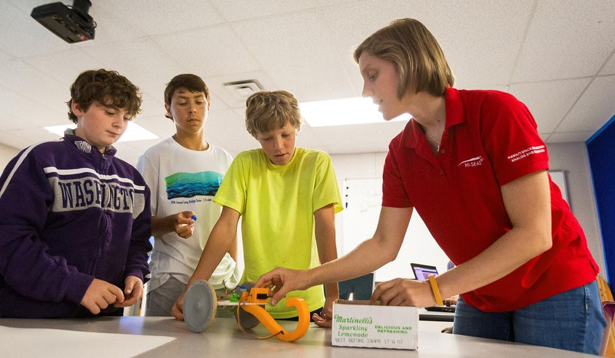 """Sophie Milam, a recent graduate of the University of Idaho, right, shows students, from left, Basquiat Nelson, Christopher Hartman and Josh Hudlet the parts of a rover she built during her eight months as the chief engineer on the HI-SEAS mission at the Rathdrum, Idaho school on Wednesday, July 15, 2015.  The 27-year-old, who lives in Smelterville and recently received her master's degree in mechanical engineering from the University of Idaho, was named by Forbes magazine among the top """"30 Under 30"""" in Science for 2015. (Shawn Gust/The Coeur D'Alene Press via AP) MANDATORY CREDIT"""