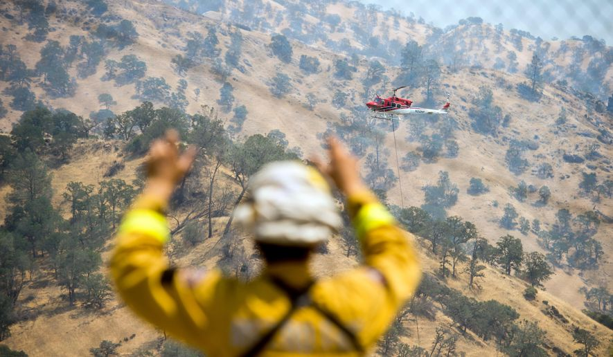 A firefighter watches a helicopter battle the Wragg fire near Winters, Calif., on Thursday, July 23, 2015. According to Cal Fire, the blaze scorched more than 6,000 acres and is threatening 200 structures. (AP Photo/Noah Berger)