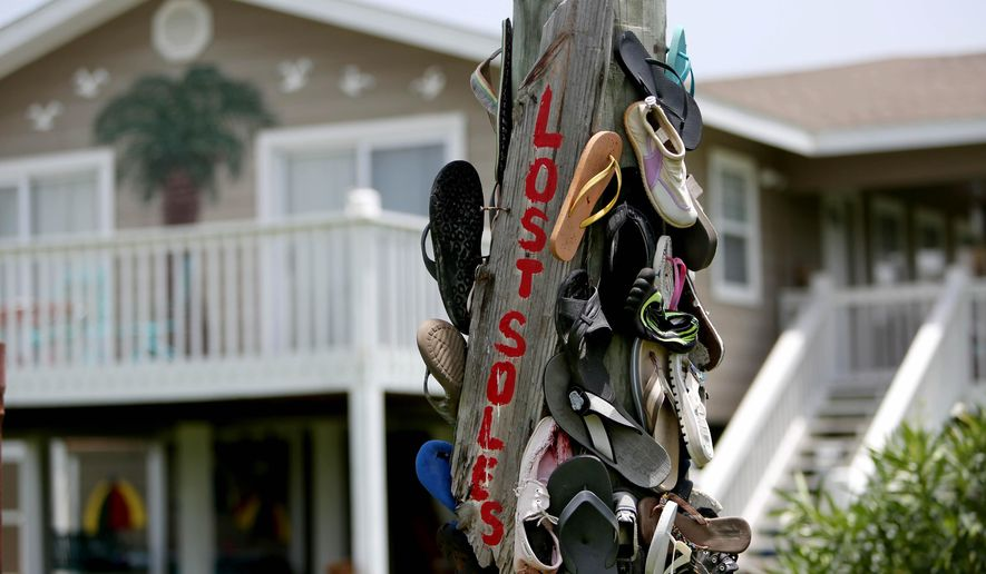 ADVANCE FOR SUNDAY, JULY 26, 2015, AND THEREAFTER - A utility pole is decorated with shoes and sandals in the Emerald Beach community, Wednesday, July 8, 2015, in Port Bolivar, Texas. New developments planned for Bolivar Peninsula, luxury houses surrounded by lush grounds and an elevated pool and a large marina, may be the future of the once rustic, fishing village along the 30-mile stretch of Highway 87. (Gary Coronado/Houston Chronicle via AP)