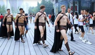 Models dressed as Spartan warriors take part in a promotional campaign by Sweetie Salad in Beijing, China, July 22, 2015. (Associated Press) ** FILE **
