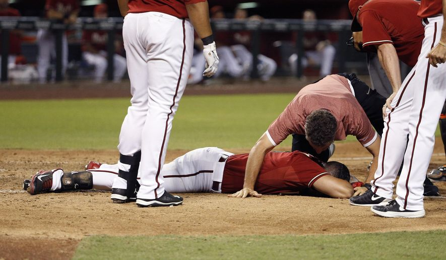 Arizona Diamondbacks' David Peralta is attended to by Diamondbacks training staff as he stays motionless on the ground after being hit in the head by a pitch during the sixth inning of a baseball game Wednesday, July 22, 2015, in Phoenix. Peralta got up under his own power but left the game. (AP Photo/Ross D. Franklin)